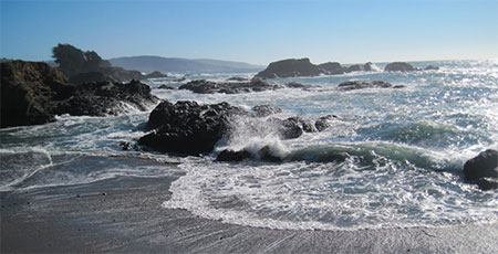 photo of rocks and waves on the beach